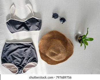 Top of black swim suit 2 peach with wide -shoulder hat , plant on pot and sunglasses on white background in flat lay of accessory beach concept