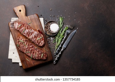 Top blade or denver grilled steak over cutting board. Top view with copy space