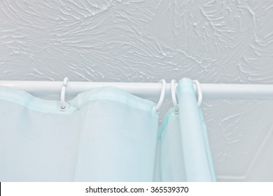 The Top Of A Blue Shower Curtain Hanging On Rail