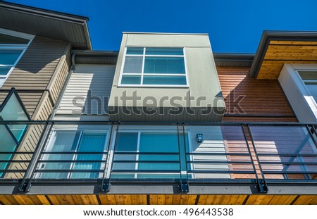 Top of brand new townhouse building on blue sky background