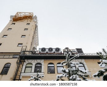 Top of the building with a tower, windows and fire ladders with snow-covered fir trees in the foreground. Bottom up view