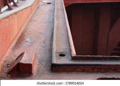 Top of the cargo hold hatch coaming with view of drainage channel and hole