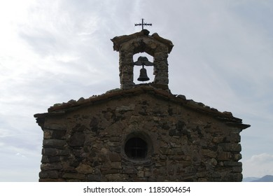 Top of a catalan, romanesque chapel facade with a one-eyed bell-gable in the center and a cross on the top, photograped against background sky