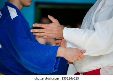 A top category judo trainer with a red-white belt teaches a young judo athlete