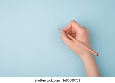 Top close up pov above overhead view photo of hand holding wooden pencil starting to draw a picture isolated over blue pastel color background
