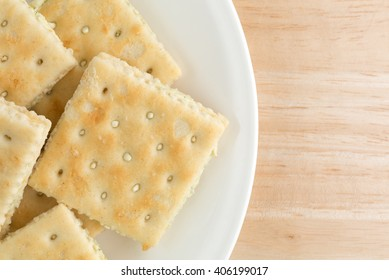 Top close view of cream cheese and chives crackers on a white plate atop a wood table top.