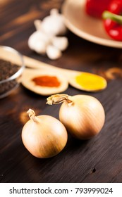 Top close up view on onions with different vegetables blurred on background over burned wooden table