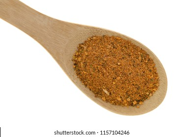 Top close view of a portion of dry brown sugar and molasses marinade mix on a wood spoon isolated on a white background.