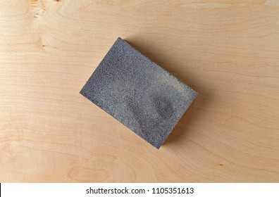 Top close view of a sanding sponge atop a piece of birch plywood.