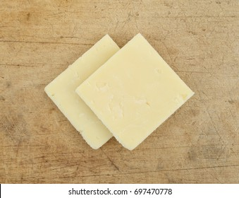Top close view of two slices of sharp cheddar cheese squares on an old worn wood cutting board.