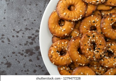 Top close view of a white plate filled with bite size bagel chips with assorted seeds on a gray background illuminated with natural light.