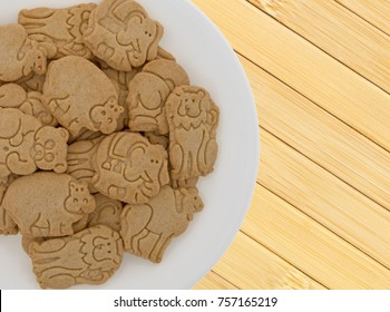 Top close view of a white plate filled with vanilla flavored animal shaped cookies on a wood place mat.