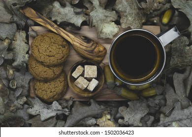Top compositions view of boiled acorn coffee in metal mug, brown sugar cubes, wooden spoon, biscuits on wooden plate and all elements surrounded with dry oak leaves and acorns