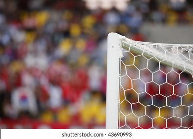 The top corner of a soccer goal in a stadium.