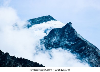 The top of a dark mountain with snow and clouds in front of it, in the French Alps