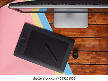 Top of designer wooden table with colourful paper and grapic table and big screen