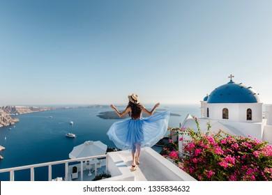 Top destination in Europe, Santorini, Greece. Beautiful woman enojing view on Santorini Island, Cyclades, Greece