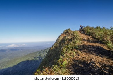Top of Doi Pha Hom Pok, Fang, Chiang Mai -THAILAND, Jan. 5, 2013 : view of a photographer standing on the top view of high mountain with blue sky background.