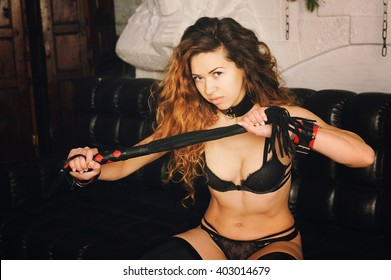 Top dominant woman portrait with flogger, sitting on a sofa, BDSM style