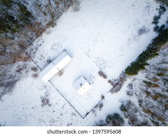 Top down aerial with buildings from above at snowy winter. Winter top down landscape with buildings form above.
