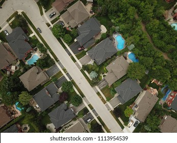 Top down aerial drone image of a suburb in the midst of summer, backyard turf grass and trees lush green.  The roofs and pools look colorful.