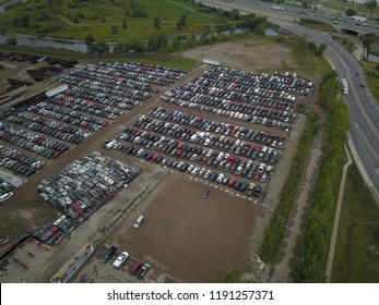 Top down aerial drone image of a junk yard with row after row of wrecked cars.