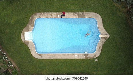 Top down aerial drone image of a backyard swimming pool surrounded by turfgrass with a swimmer in the deep end.