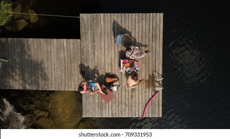 Top down aerial drone image of people sitting on a wooden dock at a cottage lake.