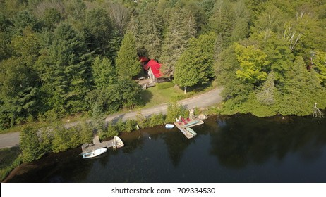 Top down aerial drone image of a cottage surrounded by dense forest on a lake with dark water and a dock.