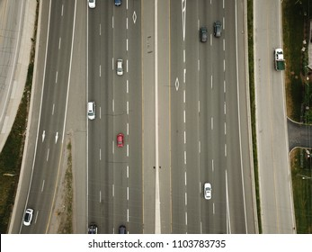 Top down, aerial drone photo of an 8 lane highway with vehicles on a sunny day.