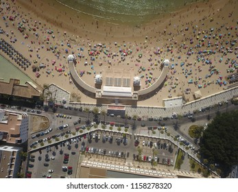 Top down aerial drone photo of Playa La Caleta, a famous beach in Cadiz, Spain, full of people and coloful umbrellas on a sunny sumer day.