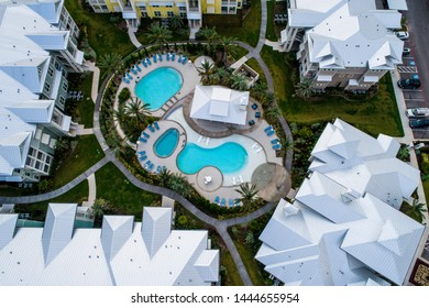 Top down aerial drone view above Moderm Condo Apartment compels with modern architecture and blue swimming pool in the middle of housing buildings