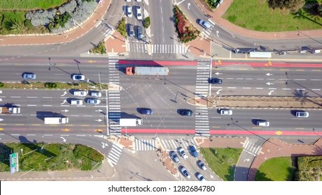Top down aerial footage of traffic on a busy Junction with cars and trucks.