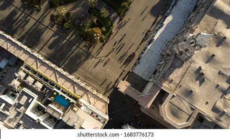Top down aerial view of Arequipa's white city main square corner - UNESCO world heritage site - white sillar cathedral, geometric park, shadows of people walking