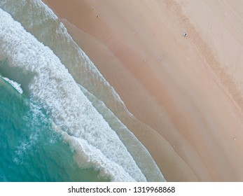 Top down aerial view of clean beach coastline.