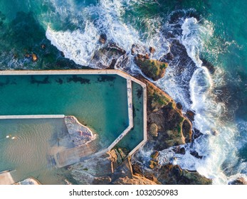 Top down aerial view of empty rock pool at Curl Curl Beach with waves surrounding it.