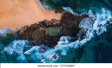 Top down aerial view of empty rock pool at Mona Vale Beach Sydney with waves crashing
