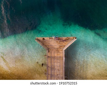 Top down aerial view. A loving couple are sitting on a wooden bridge, a pier. Sunny day, clear water, mountain lake. The concept of romance, outdoor recreation. Relationships and travel. Copy space - Shutterstock ID 1910752315