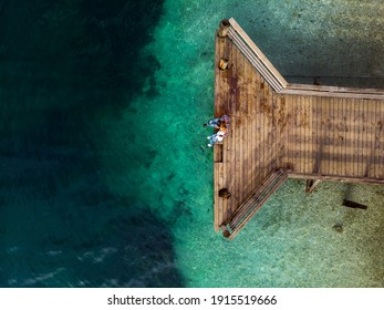 Top down aerial view. A loving couple are sitting on a wooden bridge, a pier. Sunny day, clear water, mountain lake. The concept of romance, outdoor recreation. Relationships and travel. Copy space - Shutterstock ID 1915519666
