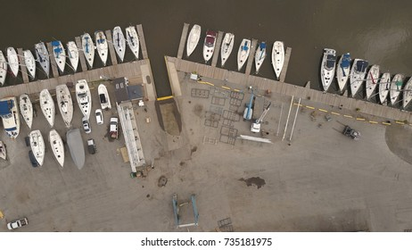 Top down aerial view of a marina with boats and heavy equipment.
