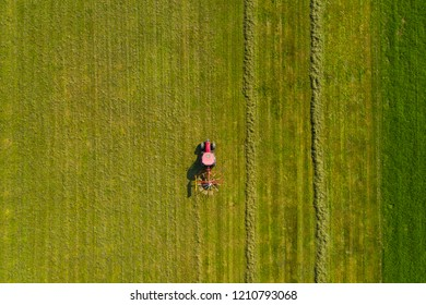 Top down aerial view of a red tractor cultivating farmland with a spinning blade in rural Slovenia