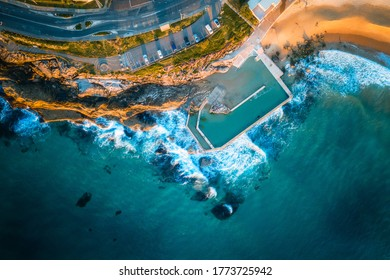 Top down aerial view of rock pool at North Curl Curl Beach Sydney with waves crashing