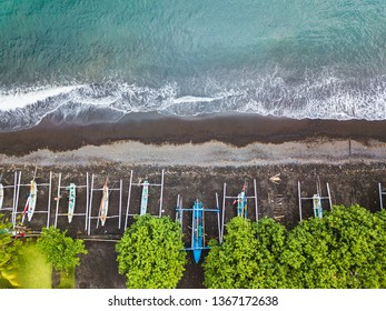 Top down aerial view of traditional Indonesian fishing boats called jukung on black sand beach. In Amed, Bali, Indonesia.