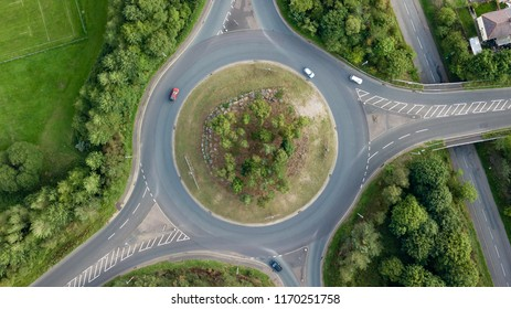 Top down aerial view of a traffic roundabout on a main road in an urban area of the UK