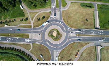 Top down aerial view of a traffic roundabout on a main road in an urban area