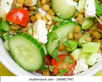 Top down close up of a healthy salad bowl. Cucumbers, tomatoes, lentils, spring onions and feta cheese.