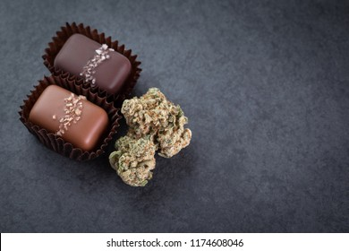 Top down close up on marijuana buds beside pot infused gourmet salted caramel edibles, with space for text on the right