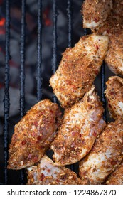Top down close up on spicy chicken wings grilling on a charcoal barbecue, in a food background