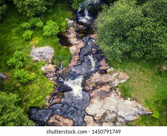 Top down drone shoot over mountain stream of Afton Rhaeadr among green plants and trees near Pistyll Rhaeadr in Snowdonia, UK