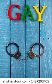 Top down image showing GAY spelt in coloured letters on a blue wooden background with handcuffs